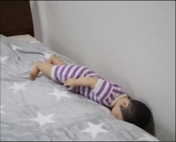 壁とベッドに赤ちゃんが挟まれている